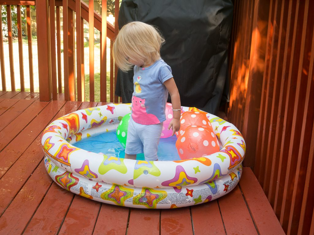 Addison testing out the baby pool on the deck